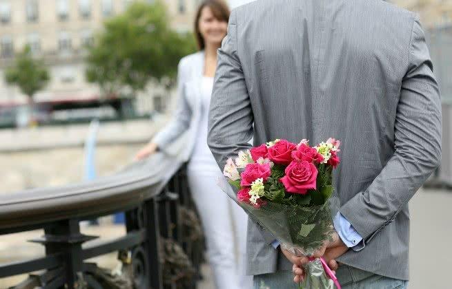 Homem entregando bouquet à mulher